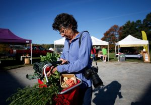 BELFAST, Maine -- 10/07/2016 -- Fine art photographer Lynn Karlin collects vegetables at the farmers market Friday in Belfast. Dan Little | BDN