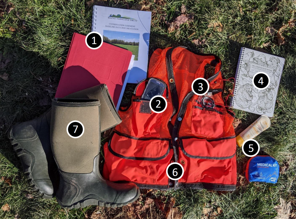 Land steward gear, including red vest, brown boots, folder, notebook, first aid kit and smartphone.