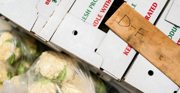 White Cardboard Boxes Of Produce Next To Bagged White And Green Cauliflower.