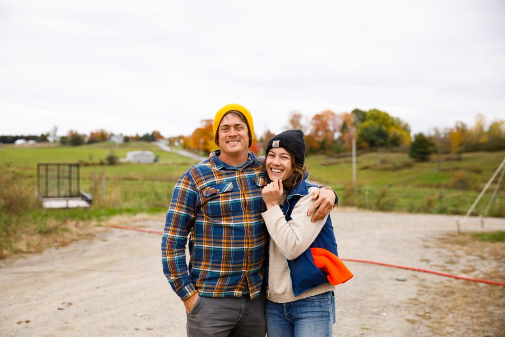 Andy and Caitlin from Milkhouse Dairy Farm, smiling with their arms around each other, on a dirt road with their farm in the background. Andy is wearing a yellow beanie, flannel shirt and dark jeans, and smiling and squinting. Caitlin is wearing a black beanie, cream jacket with a blue vest, high-vis orange object sticking out of her pocket, and blue jeans.