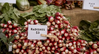 A Pile Of Red And White Radishes At A Farmers Market With A Sign That Says
