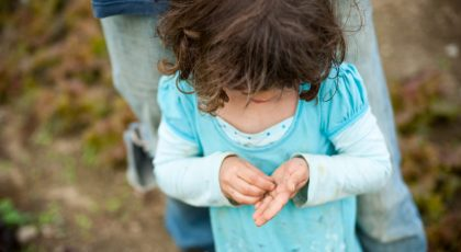 Farm Activities For Kids Include Learning About How Seeds Work. Picture: Girl With Brown Hair In Blue Dress Holding Seed In Both Hands.